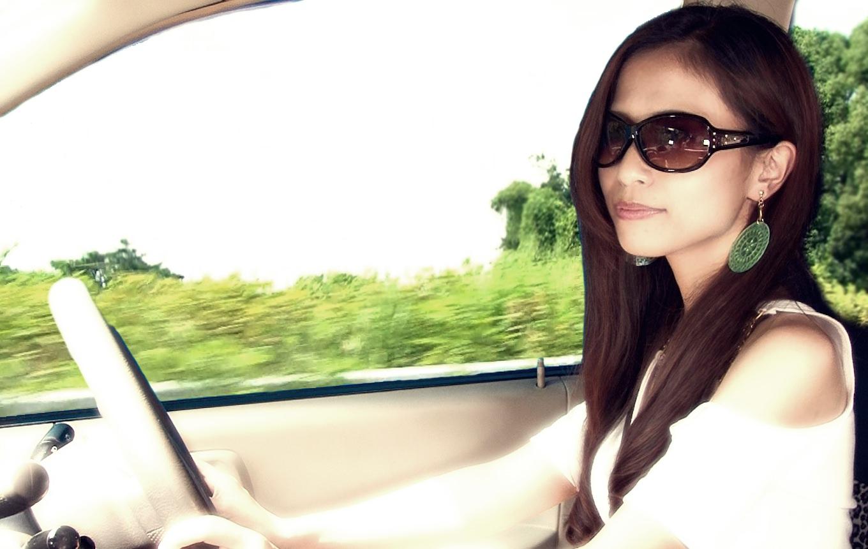 サングラスをかけて運転する女性